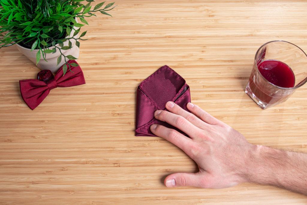 Ein rotes Einstecktuch wird auf einem Holztisch zur Dreiecksfaltung.