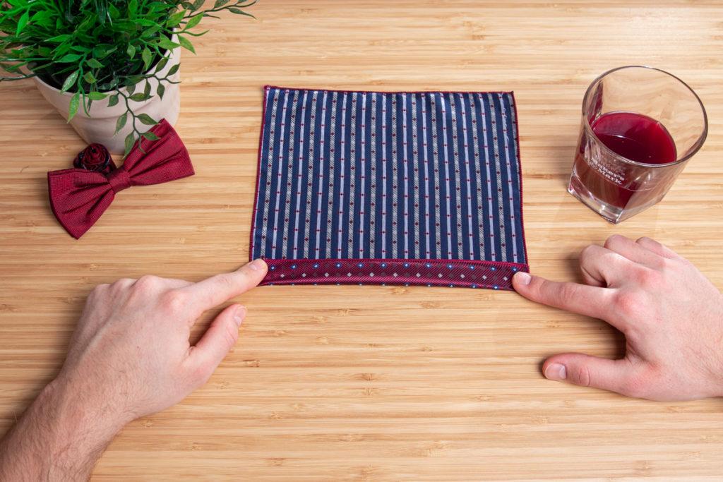 rotes Einstecktuch wird auf einem Holztisch zur Fächerfaltung gefalten.