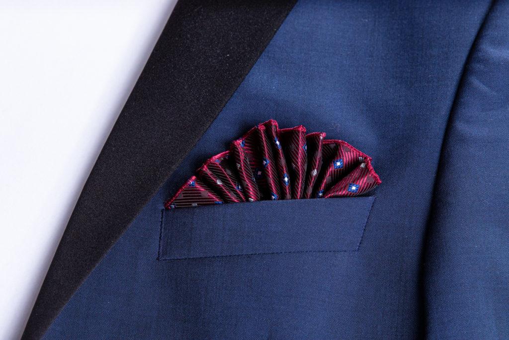 die Fächerfaltung in der Brusttasche eines Jacketts. Gehalten von einem Einstecktuch halter