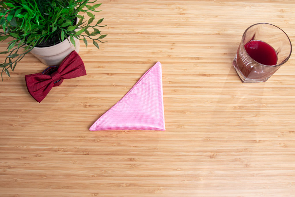 a colorful pocket square is folded on a wooden table