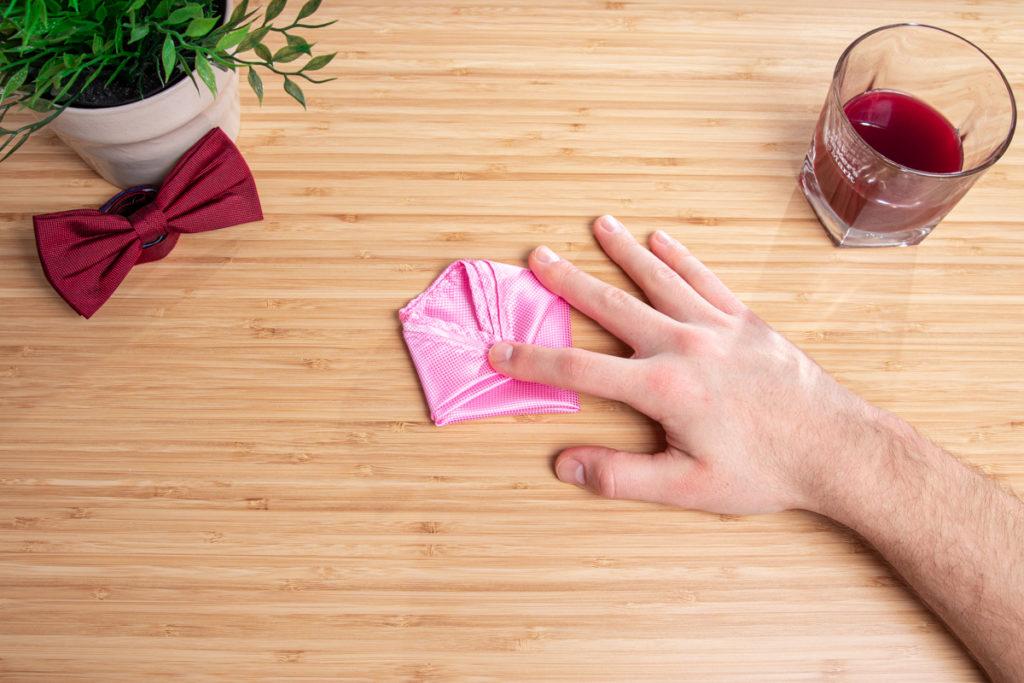 ein pinkes Einstecktuch wird auf dem Tisch gefalten.