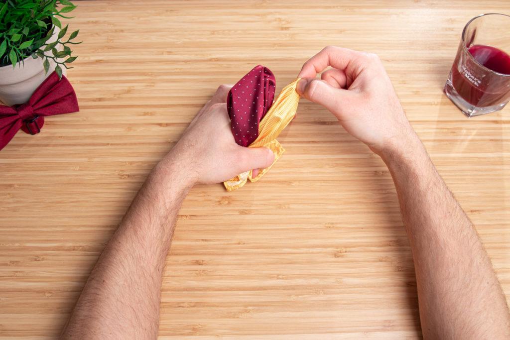 Ein Einstecktuch wird nach Anleitung zur doppelten Pufffaltung gefalten.