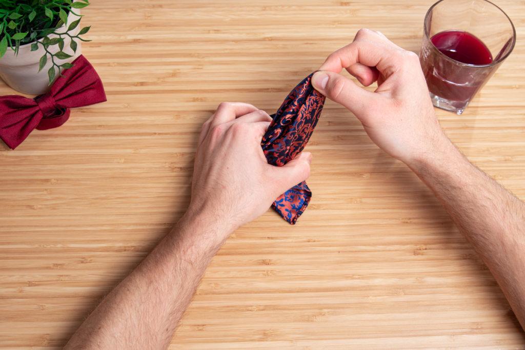 Im zweiten Schritt wird das Einstecktuch mit den Fingern durch die Hand gezogen.