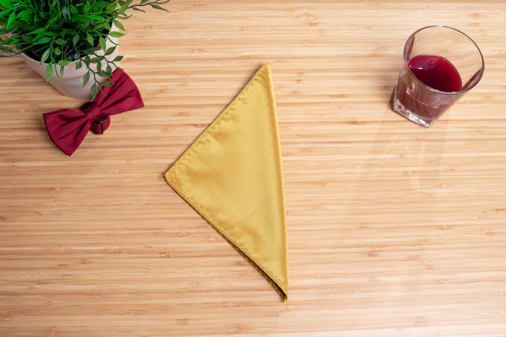 A yellow pocket square is folded to a three point fold.