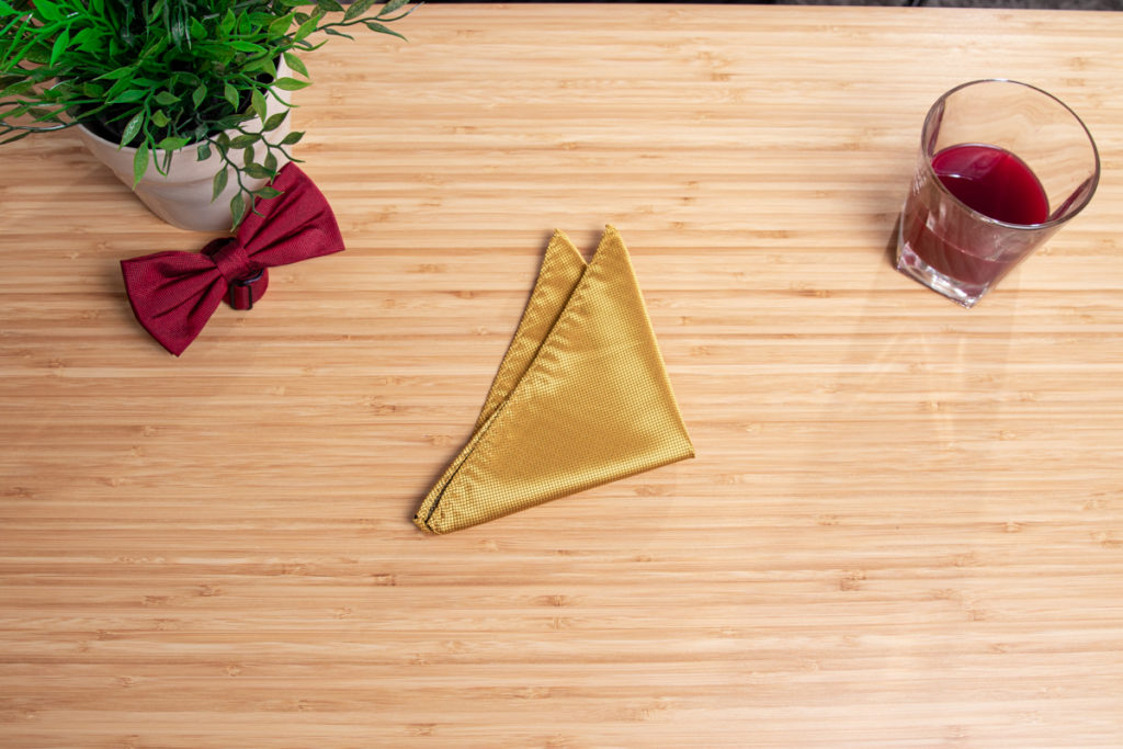 A yellow handkerchief is folded to a three point fold.