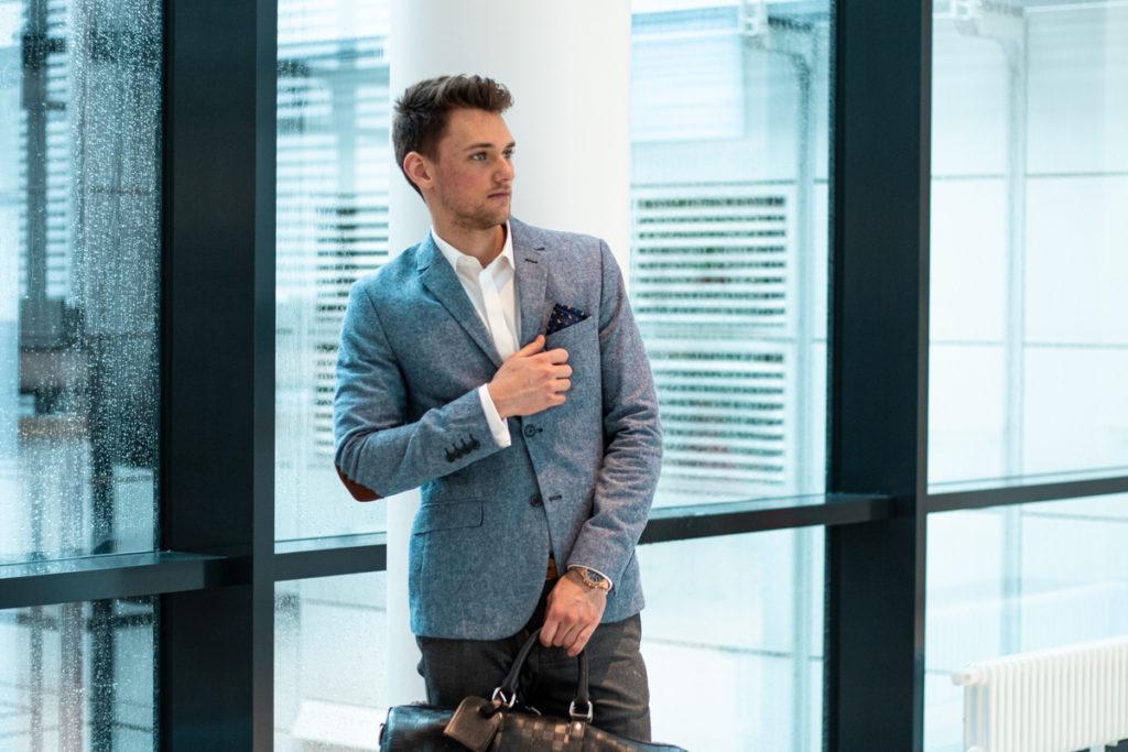 Mann mit Sacko und Tasche steht vor großer Fensterfront.