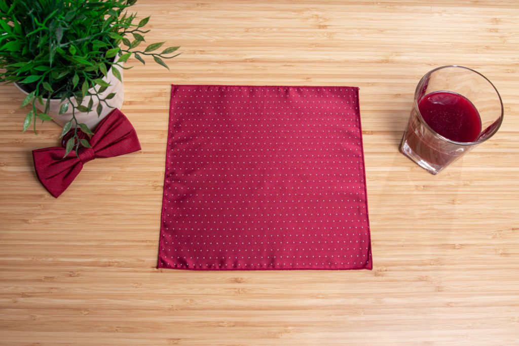 folding a red pocket square with two hand on the wooden table