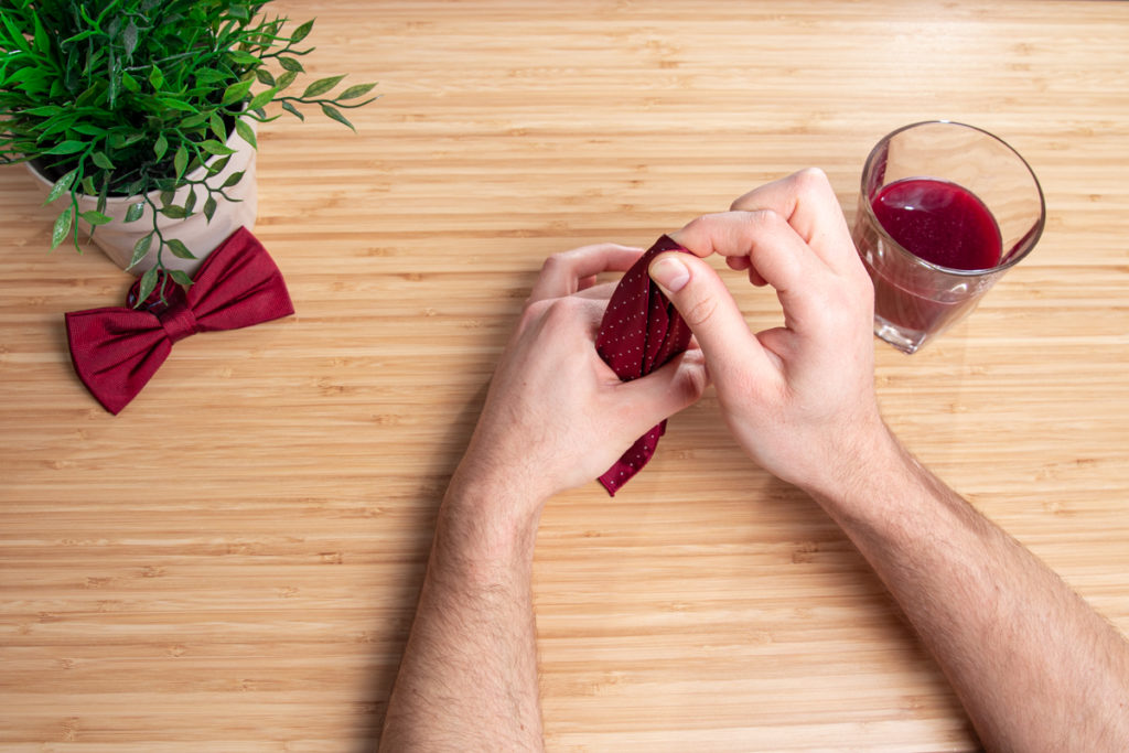 folding a red handkerchief with two hand on the wooden table