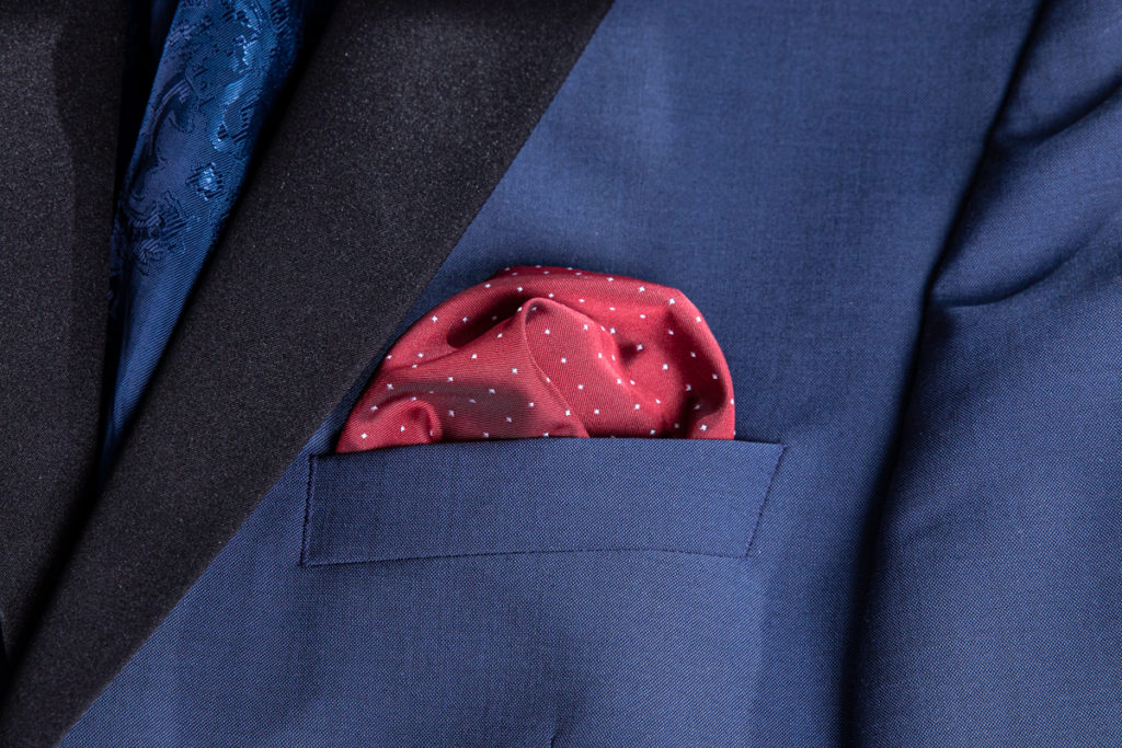 A red pocket square is already folded in a blue sacko.