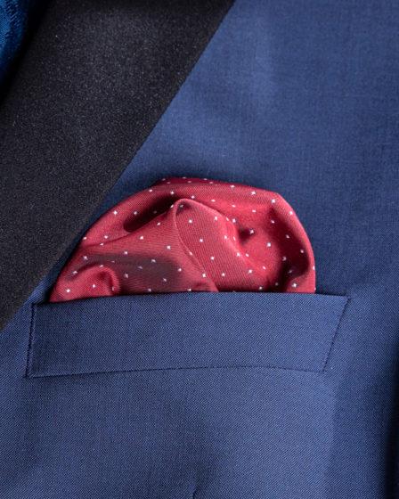 Ein rotes Einstecktuch ist fertig gefaltet in einem blauen Sacko.