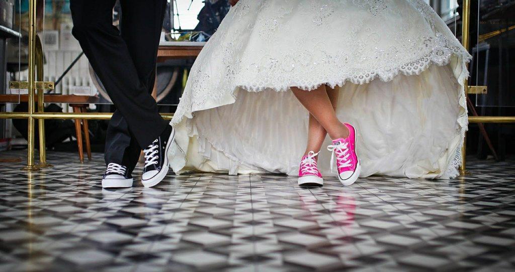 Auf dem Bild sieht man die Beine von einer Braut und einer Bräutigam. Beide tragen Converse Chucks.